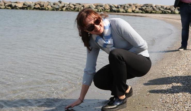 Ministrul Mediului, Apelor și Pădurilor, Cristiana Palmer, în vizită la Constanța, încercând marea cu degetul.